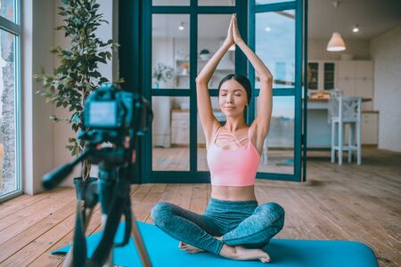 Filming yoga tutorial. Fitness trainer filming yoga tutorial for the followers in her living room Archivio Fotografico - 133528035
