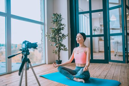 Enjoying morning. Fitness blogger feeling amazing while enjoying her morning while doing yoga and filming blog Archivio Fotografico - 133528047