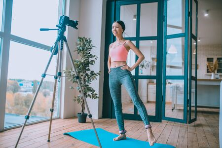 Wearing ankle weights. Dark-haired fitness trainer wearing ankle weights and filming tutorial Archivio Fotografico - 133528053