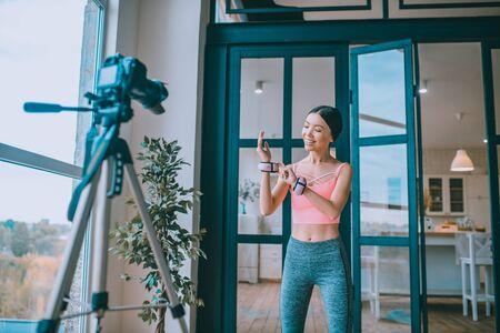 Pesas de muñeca de brazo. Entrenadora de fitness morena mostrando los pesos de su brazo y muñeca mientras filma el blog