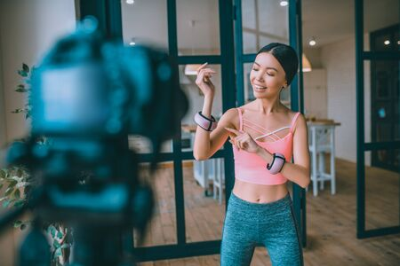About arm weights. Satisfied fitness blogger feeling good while telling followers about arm weights Archivio Fotografico - 133528061