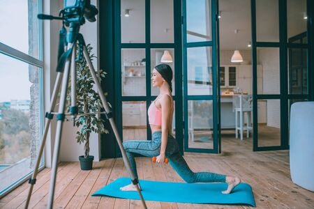 Situps with barbells. Smiling famous fitness blogger filming video doing sit ups with barbells Archivio Fotografico - 133528121