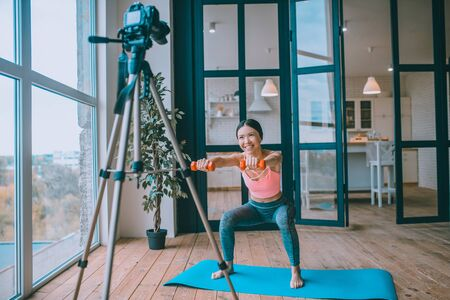 Cheerful fitness trainer. Cheerful fitness trainer smiling and doing sit ups with barbells while filming blog Archivio Fotografico - 133528120