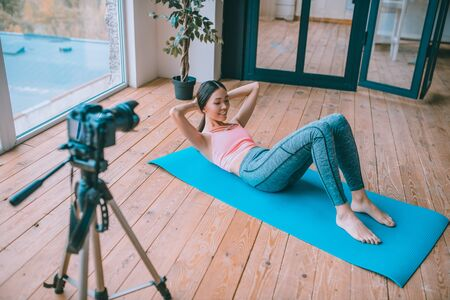 Doing abdominal crunches. Fitness blogger doing abdominal crunches while filming blog for her followers Archivio Fotografico - 133528124