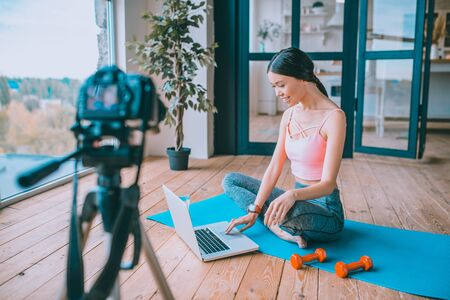 Blogger and laptop. Fitness blogger using her laptop while working on new video for her followers Archivio Fotografico - 133528128