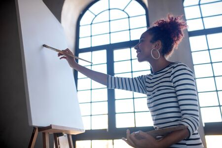 Painting on canvas. Curly young artist painting on canvas in the morning while sitting near window Archivio Fotografico - 133590808