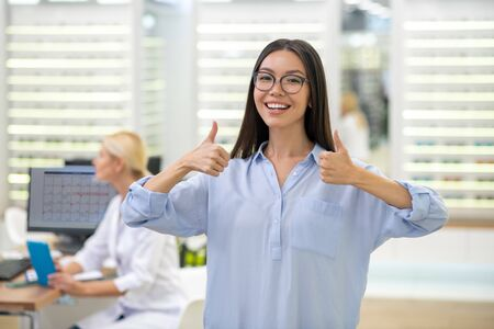 Woman feeling satisfied. Beaming appealing businesswoman feeling satisfied after visiting eye doctor and buying glasses