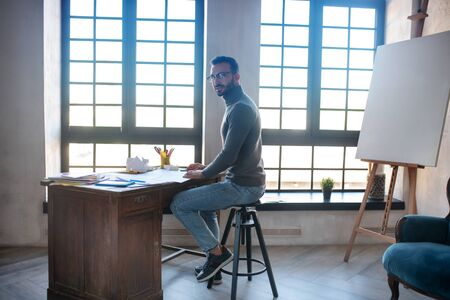 Sitting at table. Designer wearing glasses sitting at the table near drawing easel and window