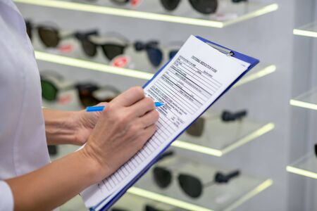 Filling medical form. Close up of eye doctor filling medical form after examining patient in the morning