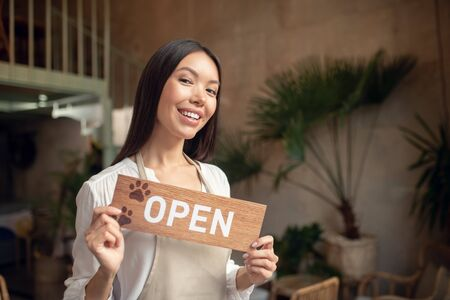 Successful entrepreneur. Excited successful entrepreneur smiling while opening her own coffee shop 写真素材