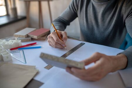Designer holding pencil. Close up of interior designer holding pencil while making sketches Reklamní fotografie