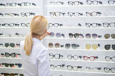 Glasses on shelves. Blonde-haired ophthalmologist wearing white coat putting glasses on shelves in optical store