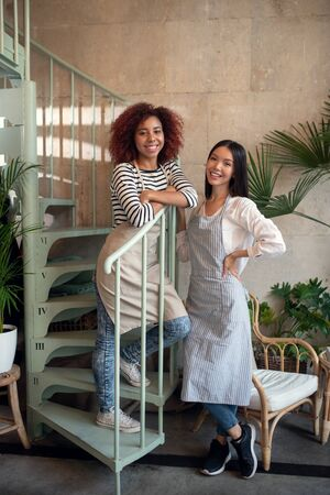 Successful businesswomen. Two successful businesswomen opening aprons opening their own coffee shop