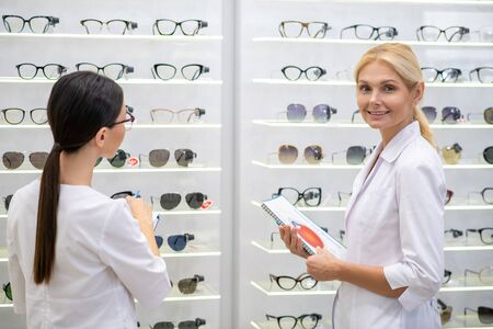 In optical store. Two ophthalmologists wearing white coats working hard while standing in optical store Imagens
