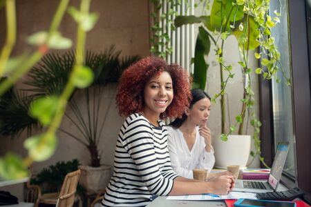Near business partner. Curly red-haired woman sitting near business partner in cafeteria