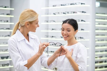 Recommending nice glasses. Blonde-haired professional eye doctor recommending nice glasses for her new assistant 写真素材