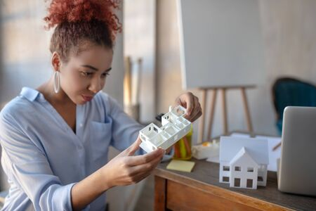 Holding apartment model. Curly stylish interior designer holding apartment model while planning new project