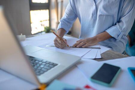Designer taking pencil. Close up of designer taking pencil while making sketches sitting near laptop 写真素材