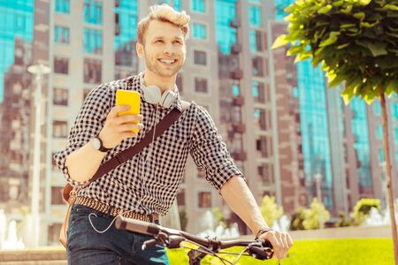 I remember. Cheerful blonde male expressing positivity while sitting on his bicycle Stok Fotoğraf