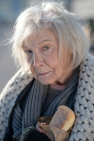 Miserable and hungry. Homeless aged woman feeling miserable and very hungry while having only bread