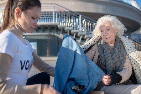 Looking at clothing. Homeless poor woman looking at clothing while volunteer bringing donation Reklamní fotografie
