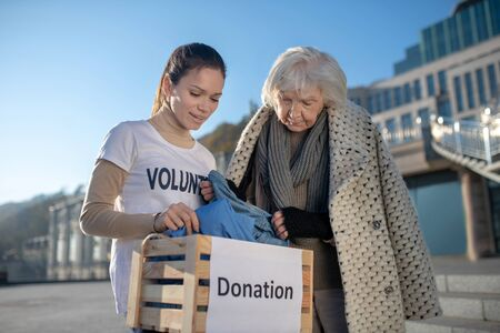 Warm old clothing. Homeless pensioner feeling thankful for warm old clothing standing near volunteer