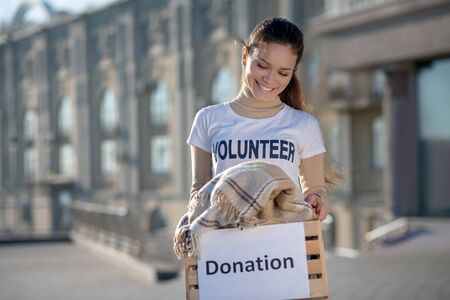 Enjoying volunteering. Beaming young dark-haired woman enjoying volunteering at the free time