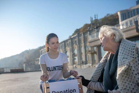 Feeling thankful. Poor homeless pensioner talking to kind young volunteer feeling thankful