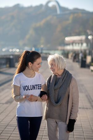 Time with volunteer. Homeless pensioner feeling good spending time with volunteer and walking together Foto de archivo
