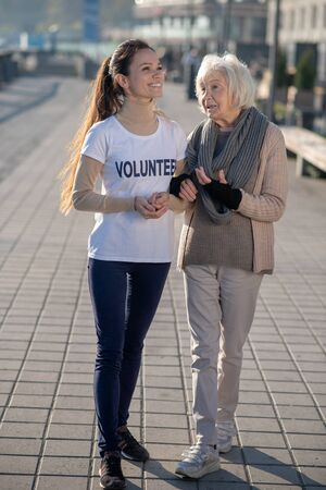 Walking and talking. Homeless woman feeling grateful while walking and talking to kind young volunteer