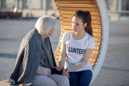 Speaking with pensioner. Volunteer wearing white t-shirt speaking with homeless pensioner sitting on bench