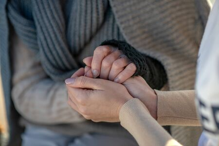 Volunteer shaking hands. Close up of kind-hearted supporting volunteer shaking hands of homeless woman