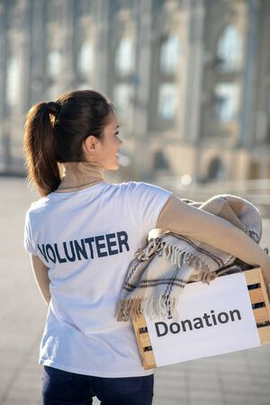 Excited before helping. Young dark-haired volunteer wearing white t-shirt feeling excited before helping people