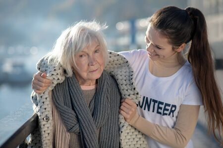 Thankful and grateful. Blue-eyed homeless pensioner feeling thankful and grateful for volunteer