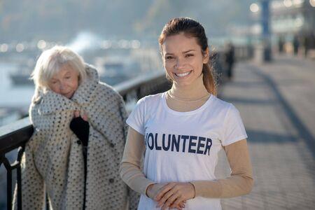 Volunteer smiling. Beaming motivated volunteer wearing white t-shirt smiling broadly after helping homeless