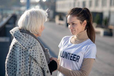Talking to volunteer. Grey-haired homeless pensioner talking to volunteer in the street while feeling grateful