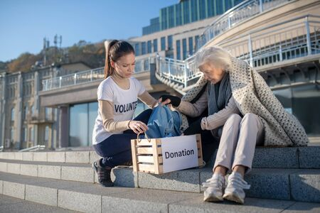 Box with donation. Dark-haired supporting volunteer bringing box with donation for homeless woman Reklamní fotografie