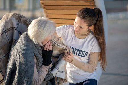 Volunteer bringing plaid. Caring supporting volunteer bringing plaid for homeless woman feeling cold