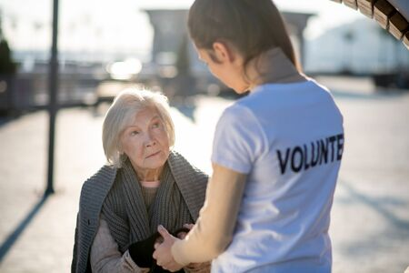 Pensioner and volunteer. Homeless aged hungry pensioner talking to volunteer in the street