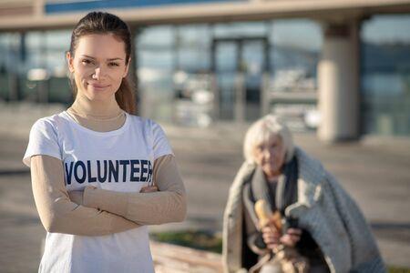 Feeling motivated. Dark-eyed volunteer wearing white shirt feeling motivated while helping homeless Reklamní fotografie