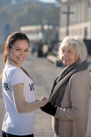 Supporting and helping. Smiling positive volunteer supporting and helping poor homeless woman