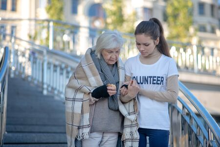 Helping homeless. Young kind volunteer helping homeless with plaid on shoulders woman to walk Reklamní fotografie