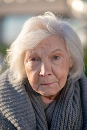 Feeling unprotected. Aged grey-haired homeless woman with facial wrinkles feeling unprotected