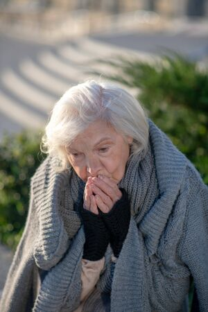 Homeless pensioner. Grey-haired homeless pensioner feeling very cold and hungry outside Stock Photo