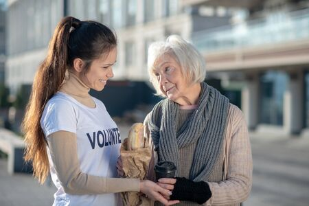 Supporting poor woman. Kind-hearted volunteer supporting poor woman while bringing bread and tea