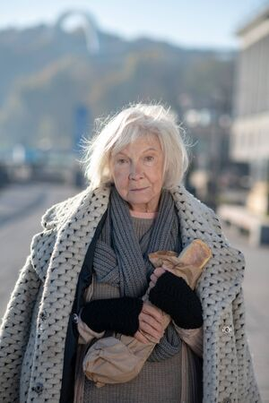 Woman holding bread. Poor homeless woman wearing warm coat holding bread while feeling hungry