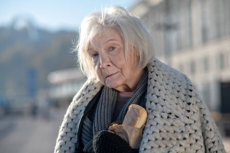 Coat on shoulders. Grey-haired homeless woman with coat on shoulders holding bread