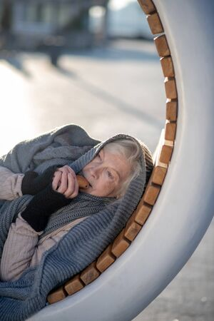 Pensioner eating cracker. Poor hungry pensioner eating cracker while lying on bench outside