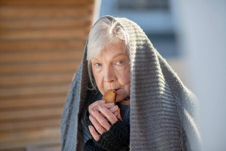 Eating little cracker. Aged homeless woman eating little cracker while feeling hungry