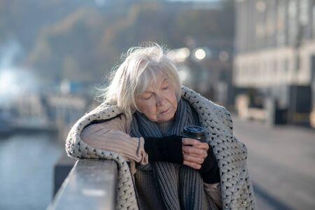 Standing on bridge. Grey-haired homeless woman feeling miserable while standing on the bridge and drinking tea Reklamní fotografie
